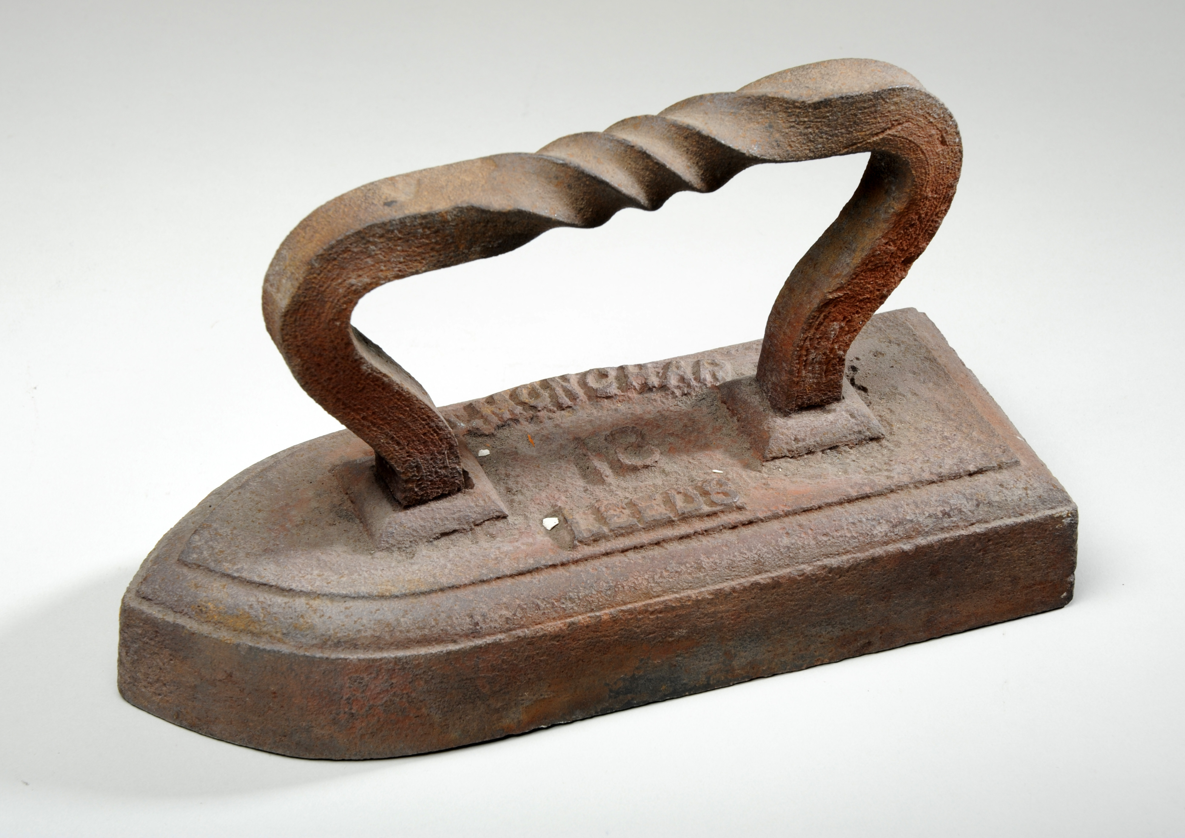 Solid metal iron with a twisted metal handle