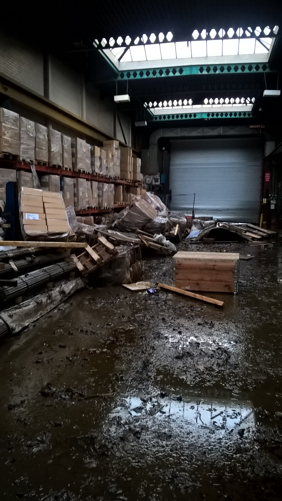 Colour photograph showing a warehouse with goods stacked up on the left hand side.  The floor is covered in thick mud and many boxes and pallets are strewn around