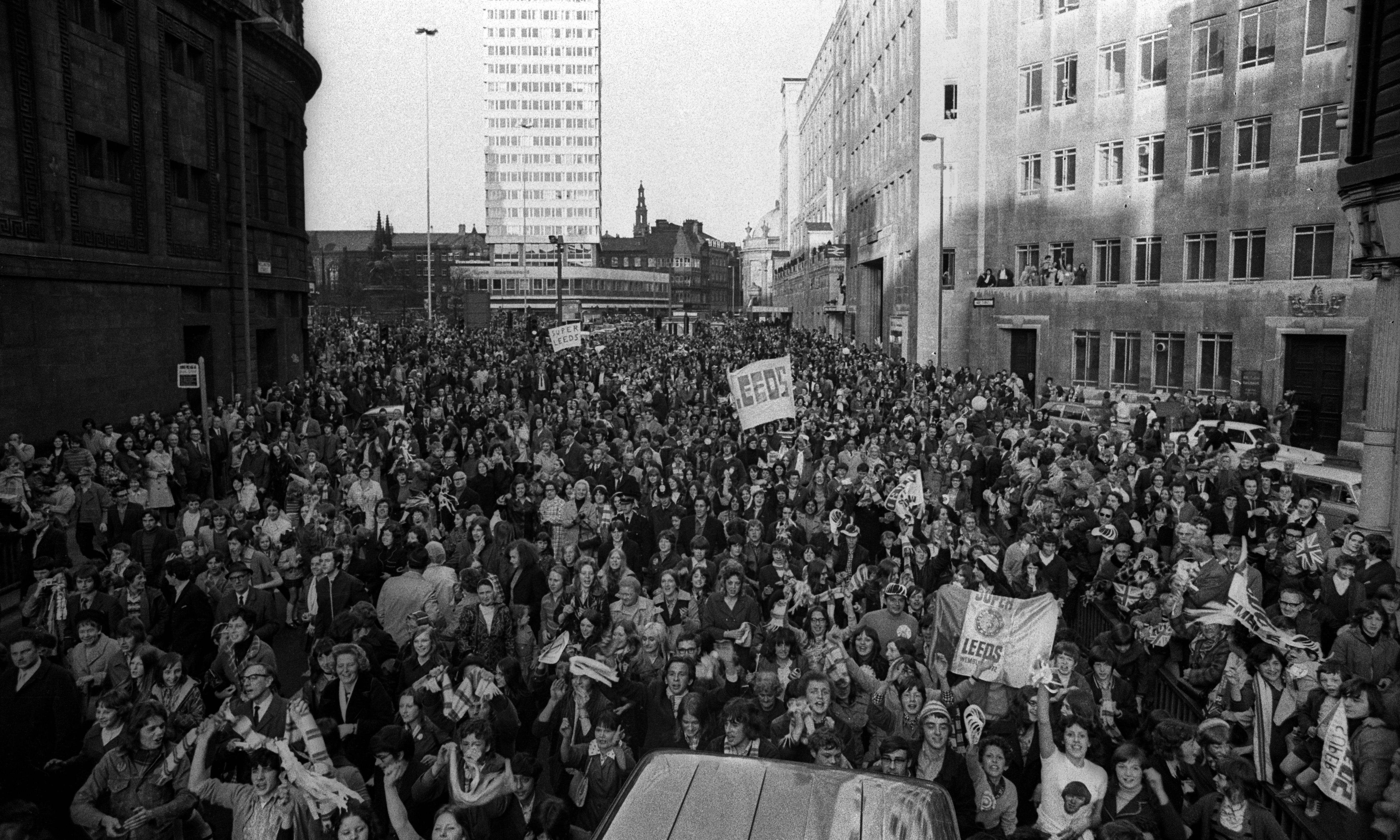 Black and white photograph showing streets of Leeds full of people celebrating