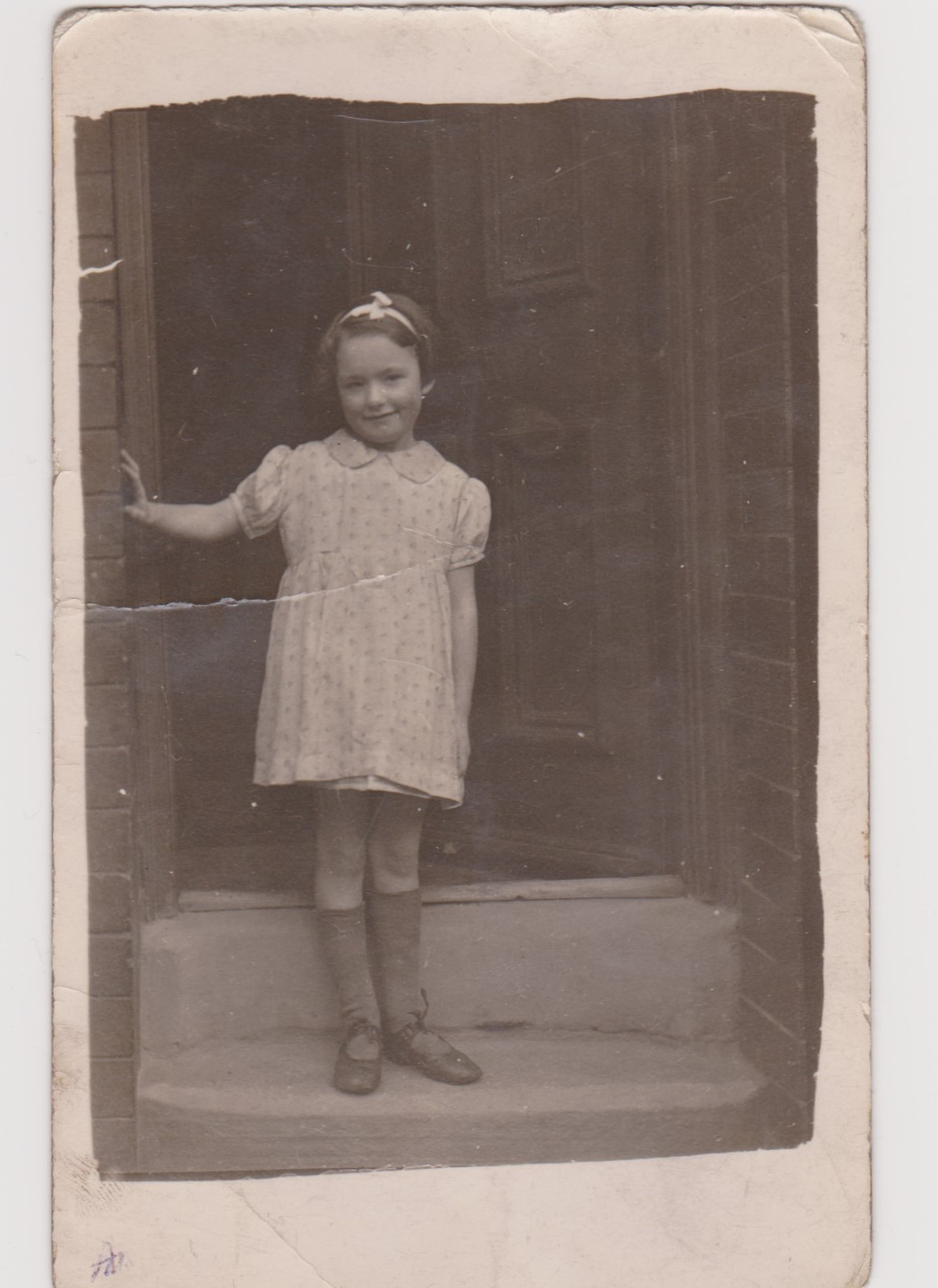 Photo of Annie Clarke standing on the doorstep of her house in Marley Place, Beeston