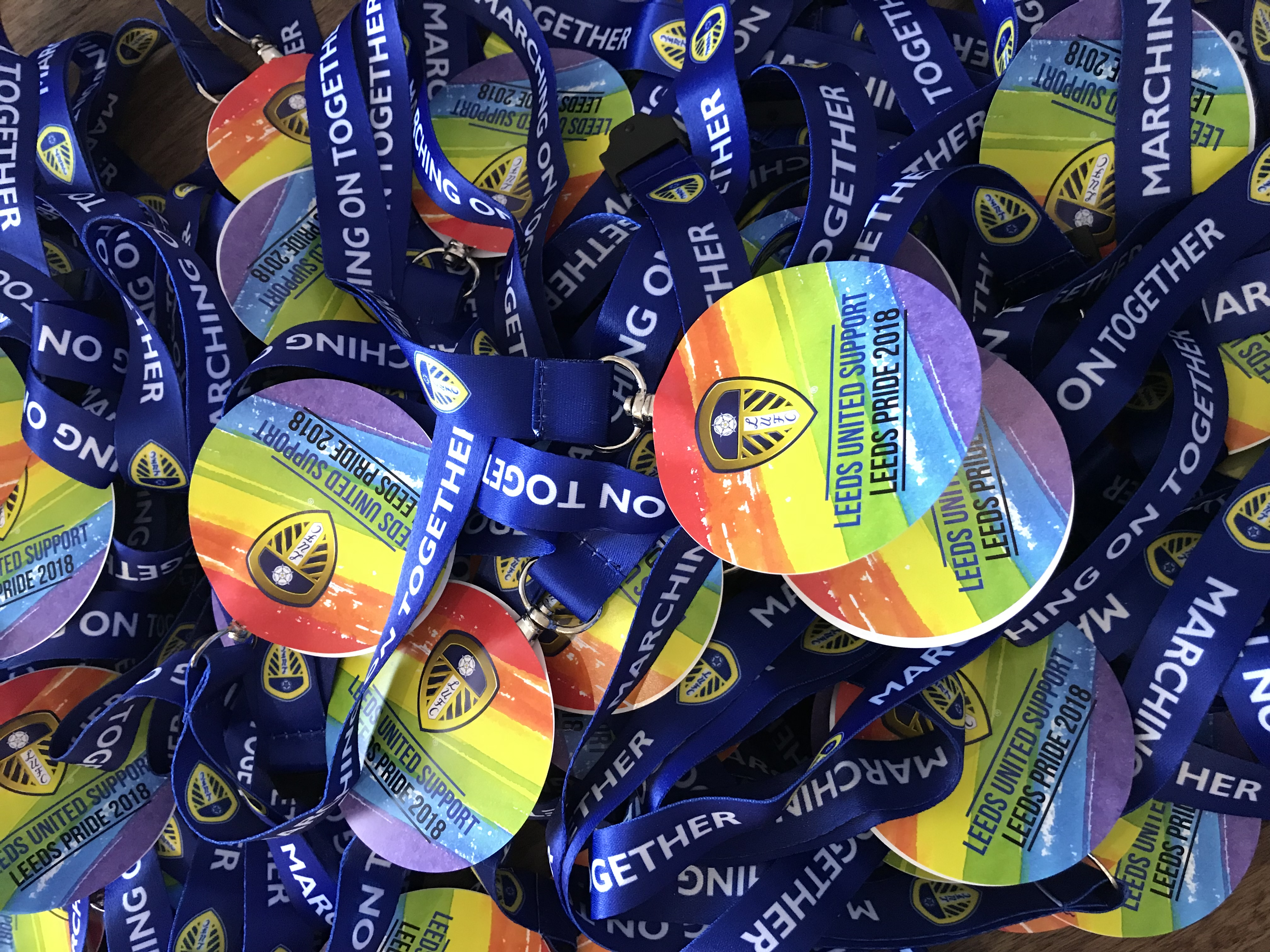 Colour photograph showing a large pile of lanyards with rainbow discs and the Leeds United logo on.