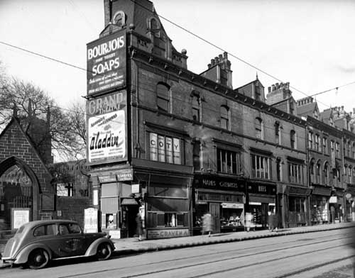 Black and white photograph of a street scene, with a car and shops.