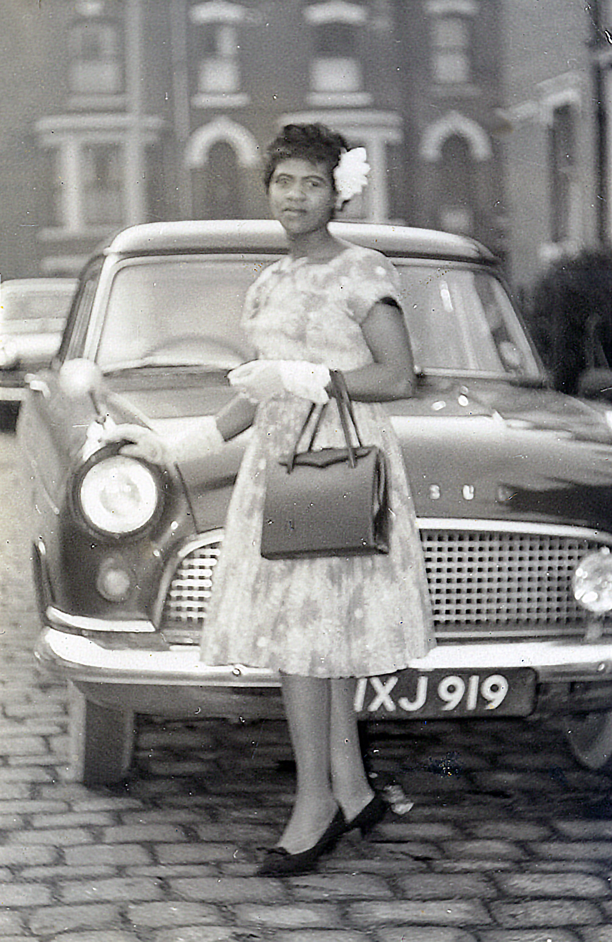 Black and white photograph showing a young woman in a white dress and gloves, standing in front of a car.