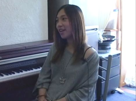Colour photograph of a woman with long straight hair, sitting in front of a piano