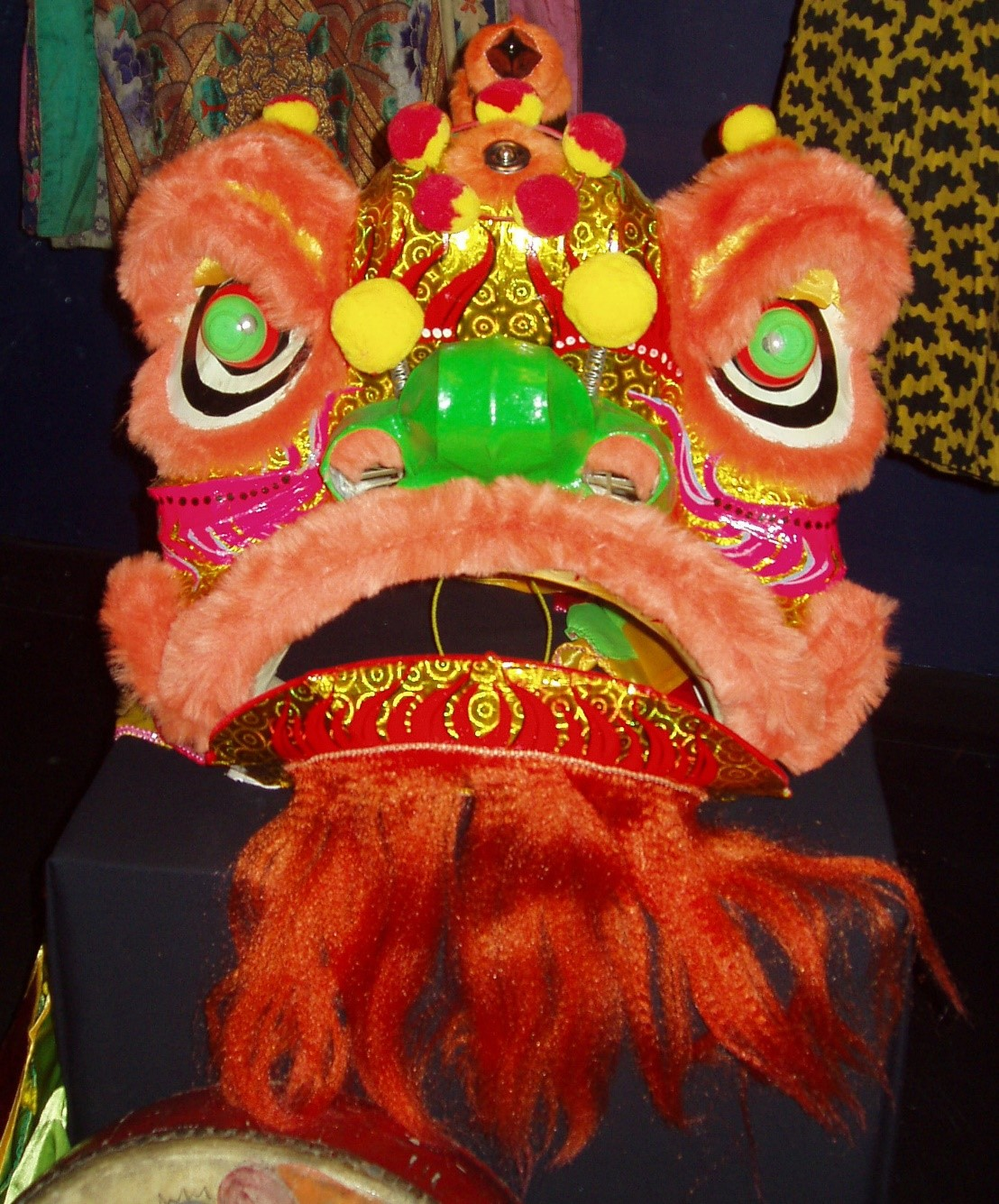 Large mask used for traditional Chinese lion dance. The lion is red pink and yellow with green eyes and nose and has a mouth that opens and closes.