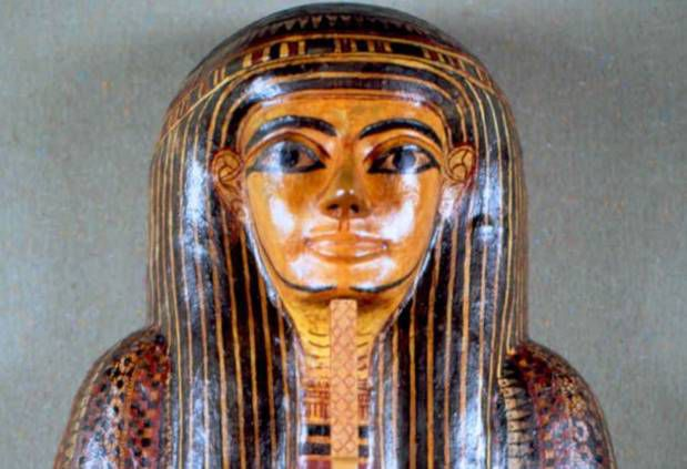 Head of a Mummy case found at Thebes.  The head has heavily made up eyes and a long, thin beard