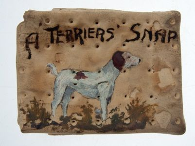 WW1 army ration biscuit decorated with a terrier dog and the words 'A Terrier's Snap'