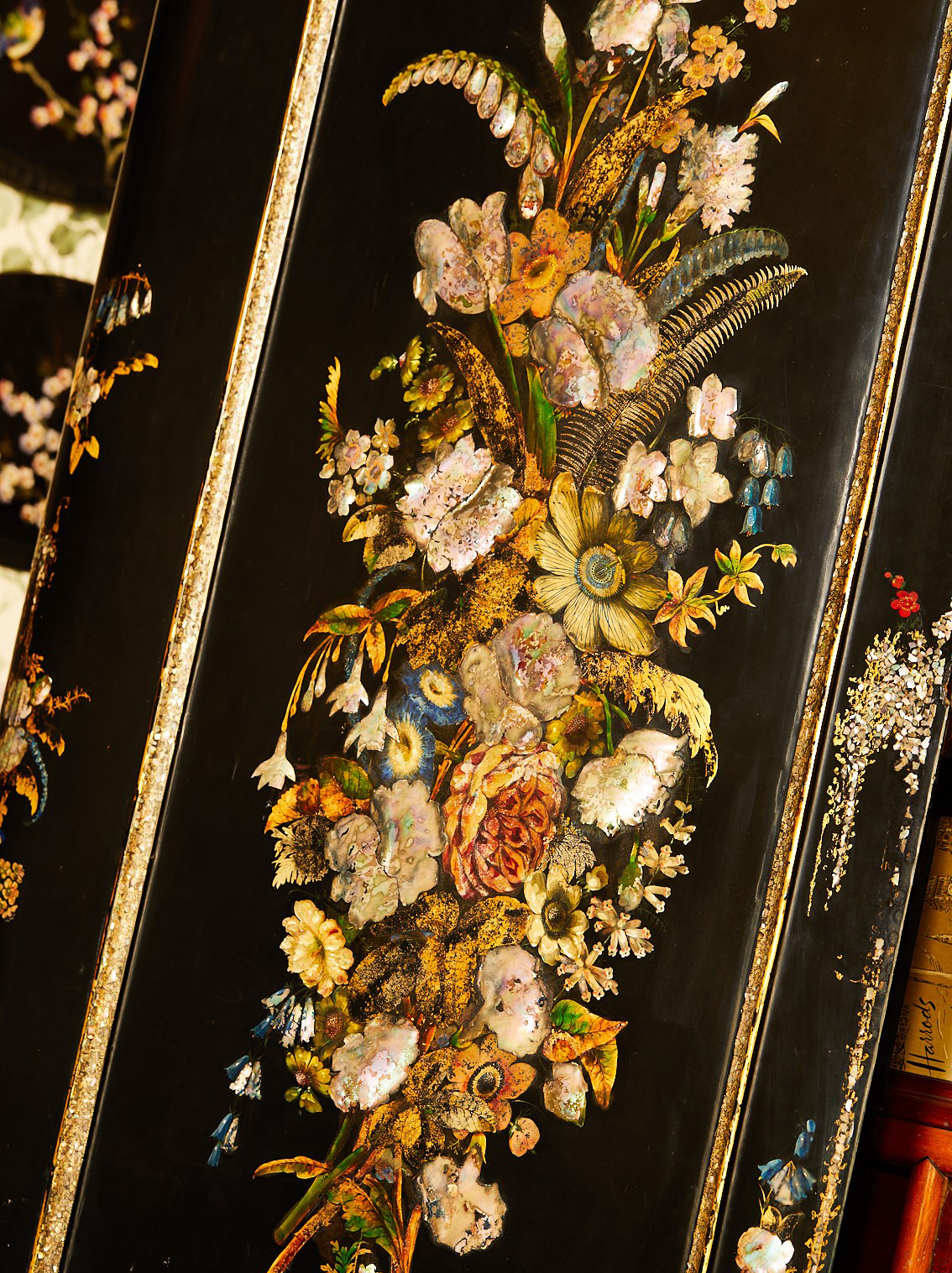 Close up showing painted flowers on a black papier mache background