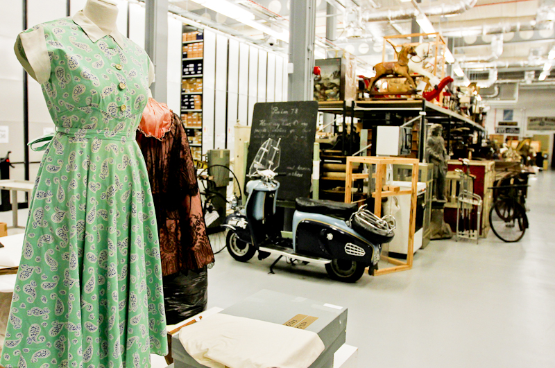 Colour photograph showing a view of the museum store, with a dress ,boxes  and shelves of objects.
