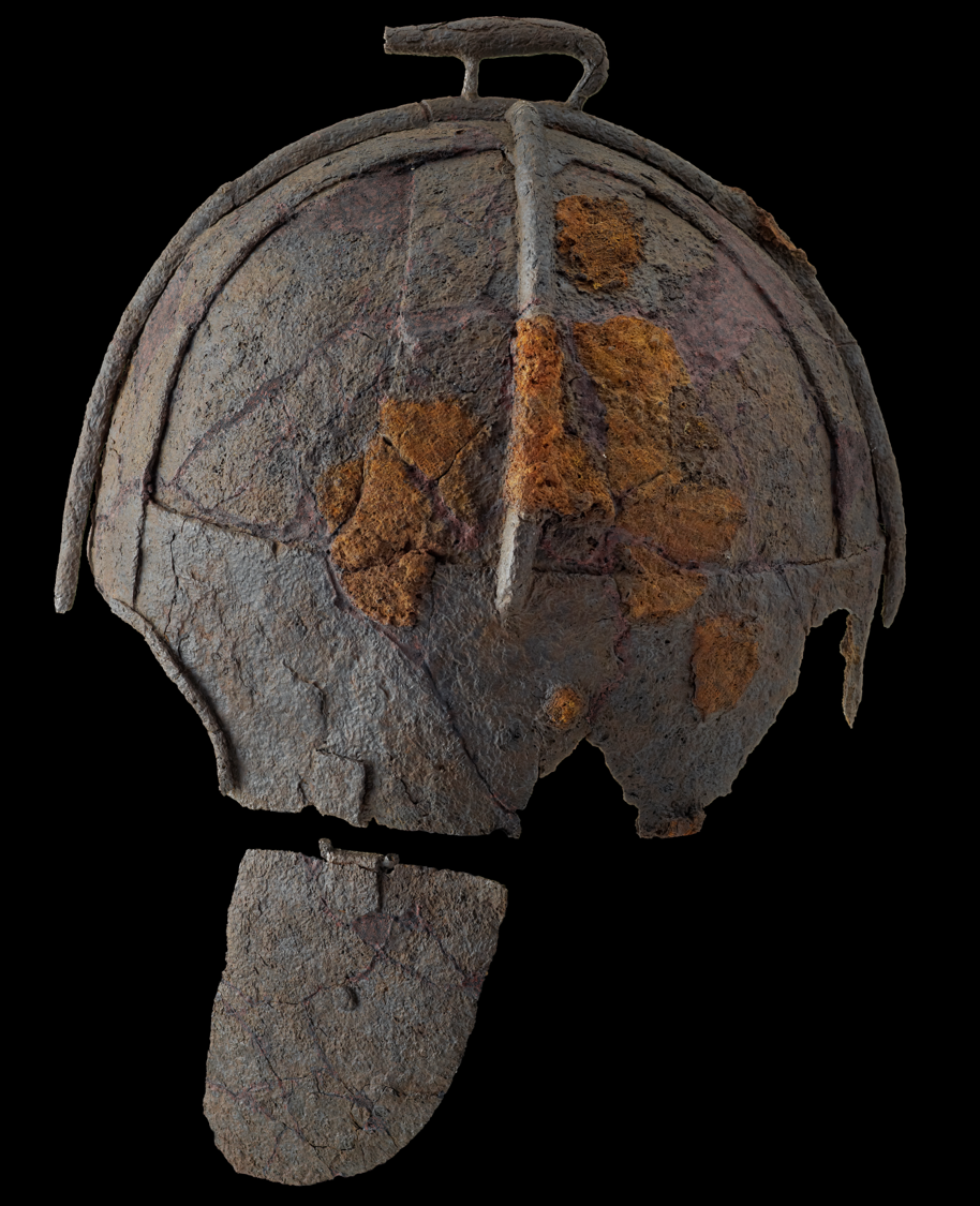 Grey helmet photographed from the side, with a small boar on the crest