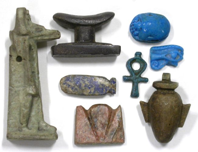 An Assortment of small  Egyptian Amulets including eye of Horus, a small bottle and a neck rest.