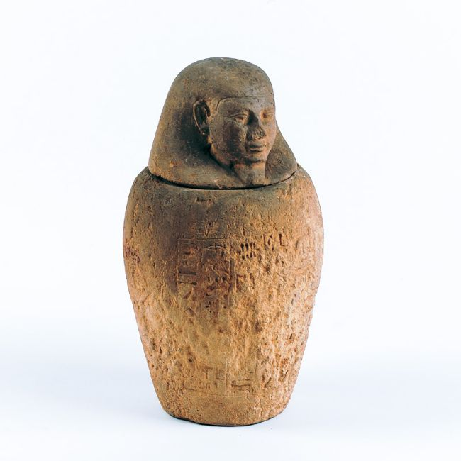 Carved stone jar with lid carved in the shape of a human head.