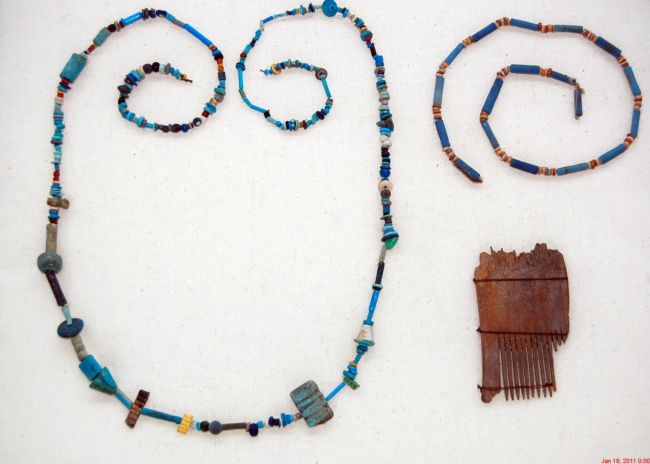 Necklace made from assorted shaped beads in mostly blue colours, with a bit of a wooden comb showing very fine teeth
