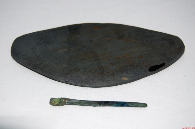 Flat piece of slate that has been shaped into an oval.  The probe is long and thin piece of copper with a flatter bit at one end.