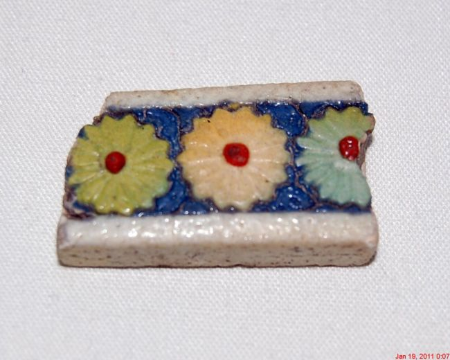 Piece of tile with white edges top and bottom and a blue stripe down the middle.  In the stripe are different coloured flowers