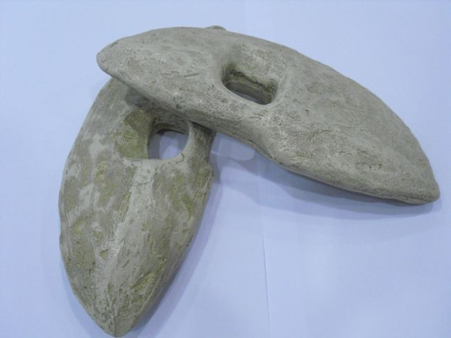 Lozenge shaped stone weights with holes drilled through the middle for attachment