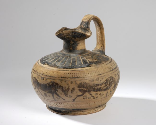 Squat shaped jug with handle and narrow neck.  Goats have been painted around the outside in black slip