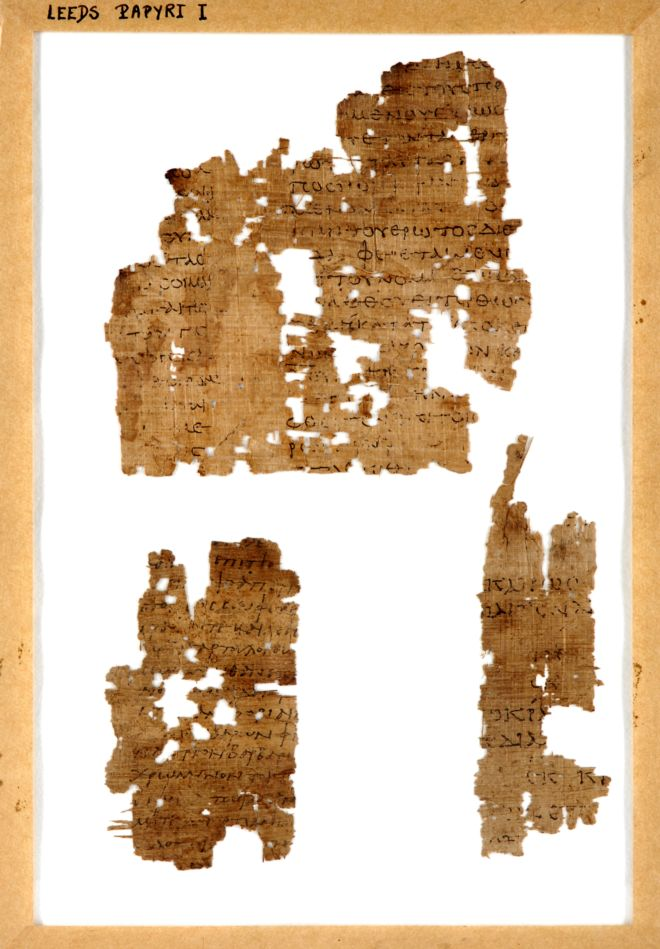 A fragment of papyrus, torn and with holes in it.  The writing is still visible in black ink.