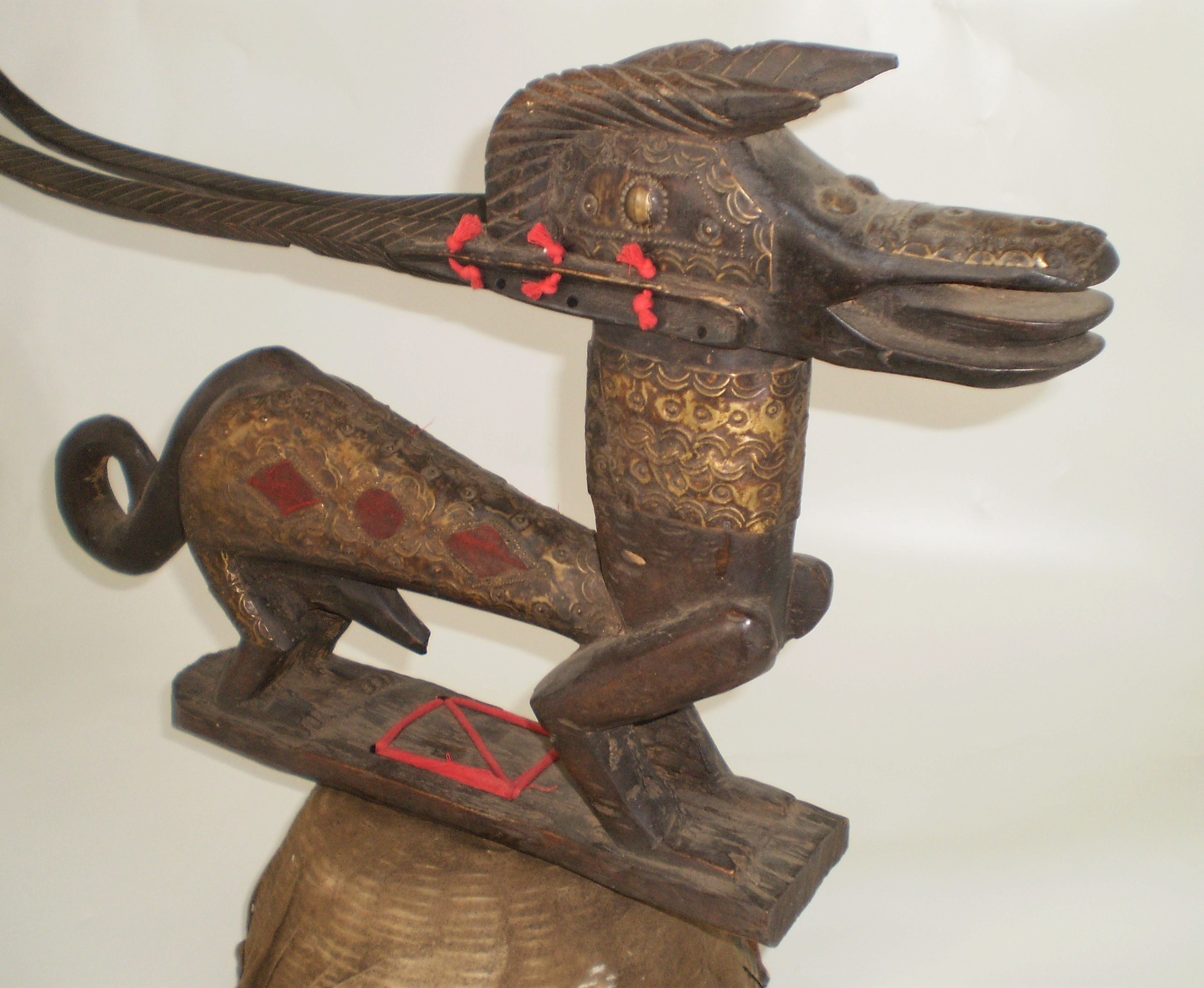 Wooden carved dog with a woven base that can be worn on the head.