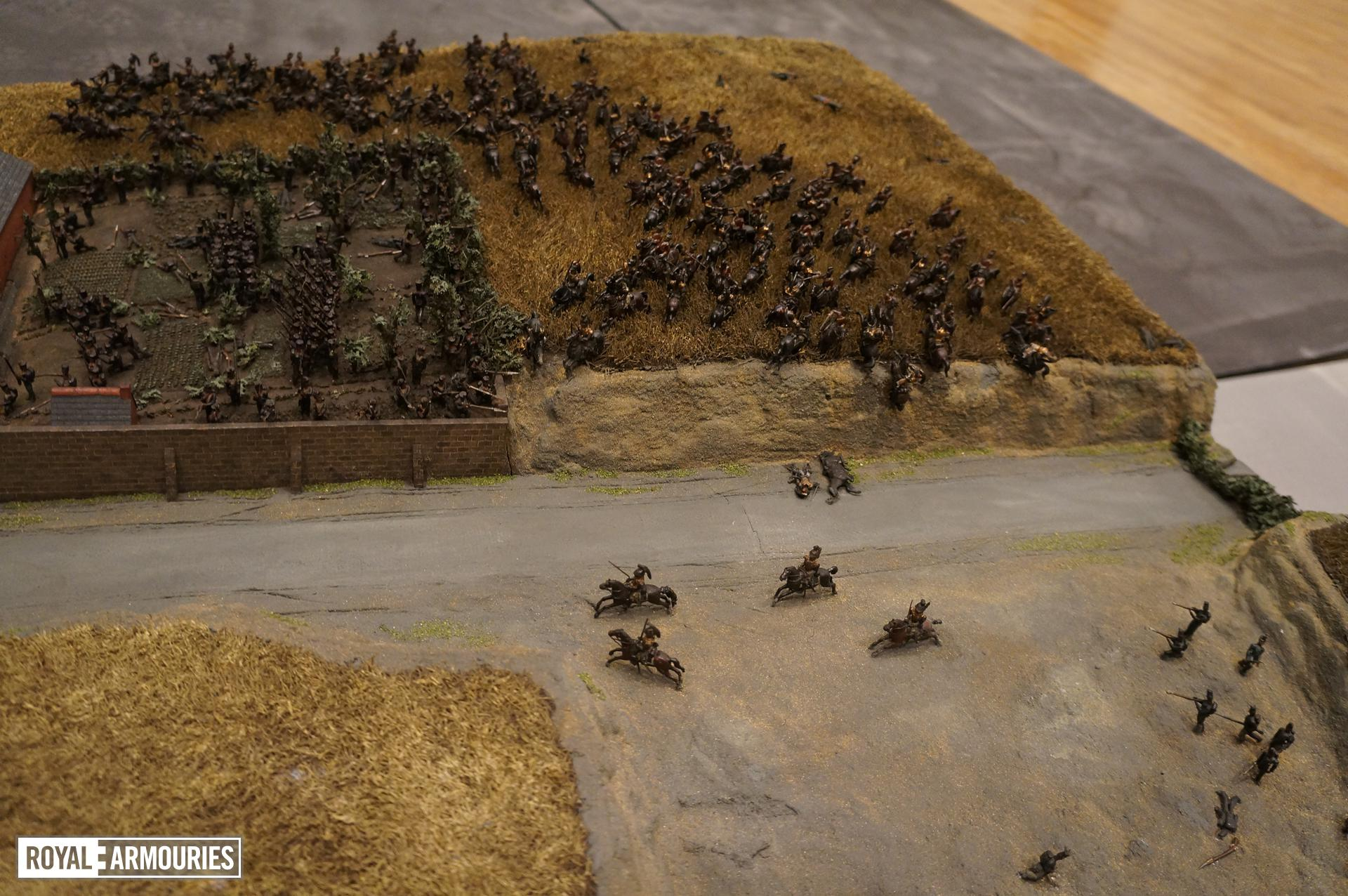 Close up photograph showing several model soldiers fighting in farm roads and fields, some on horseback