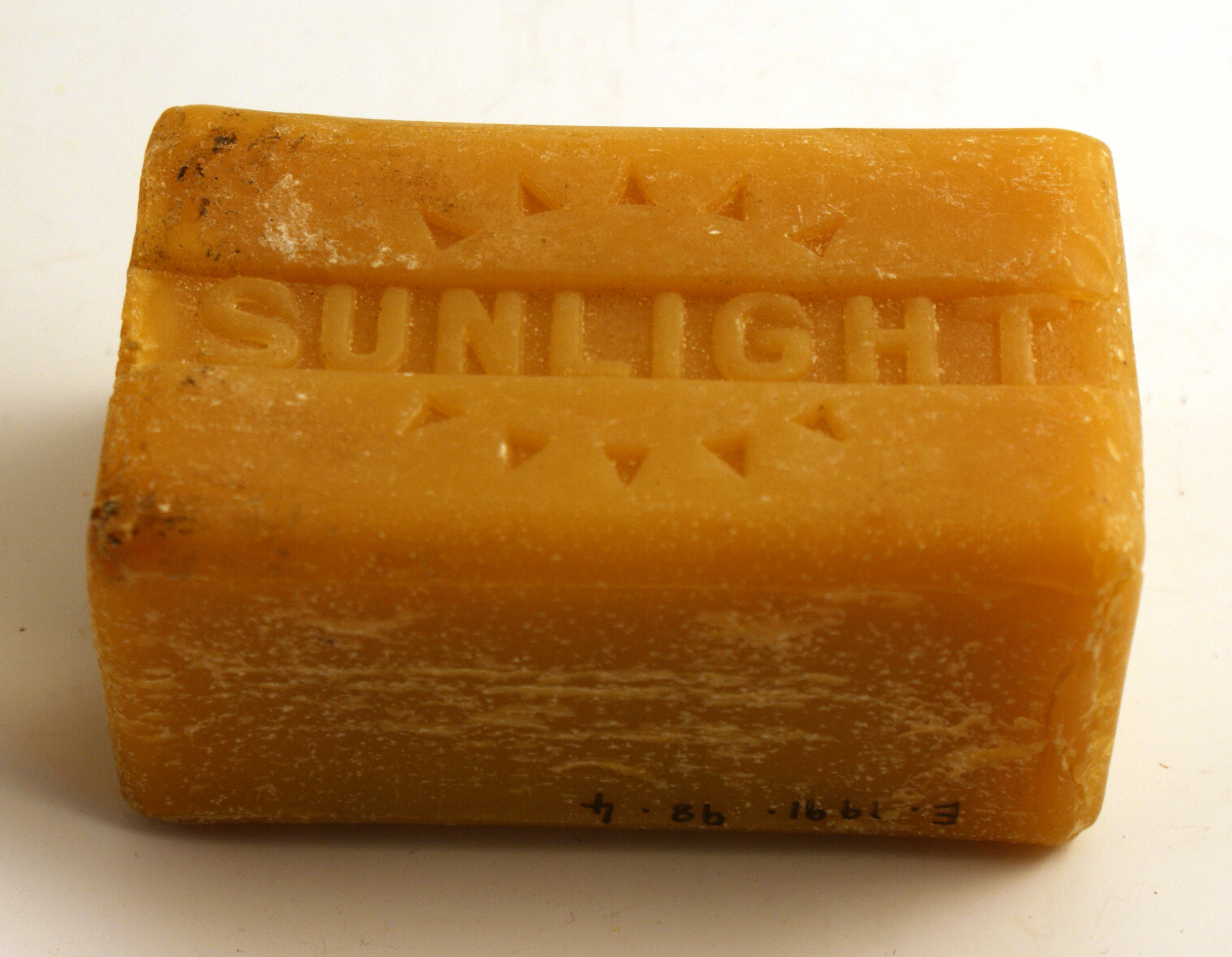 Bar of orange coloured solid soap with the word 'Sunlight' embossed on it.