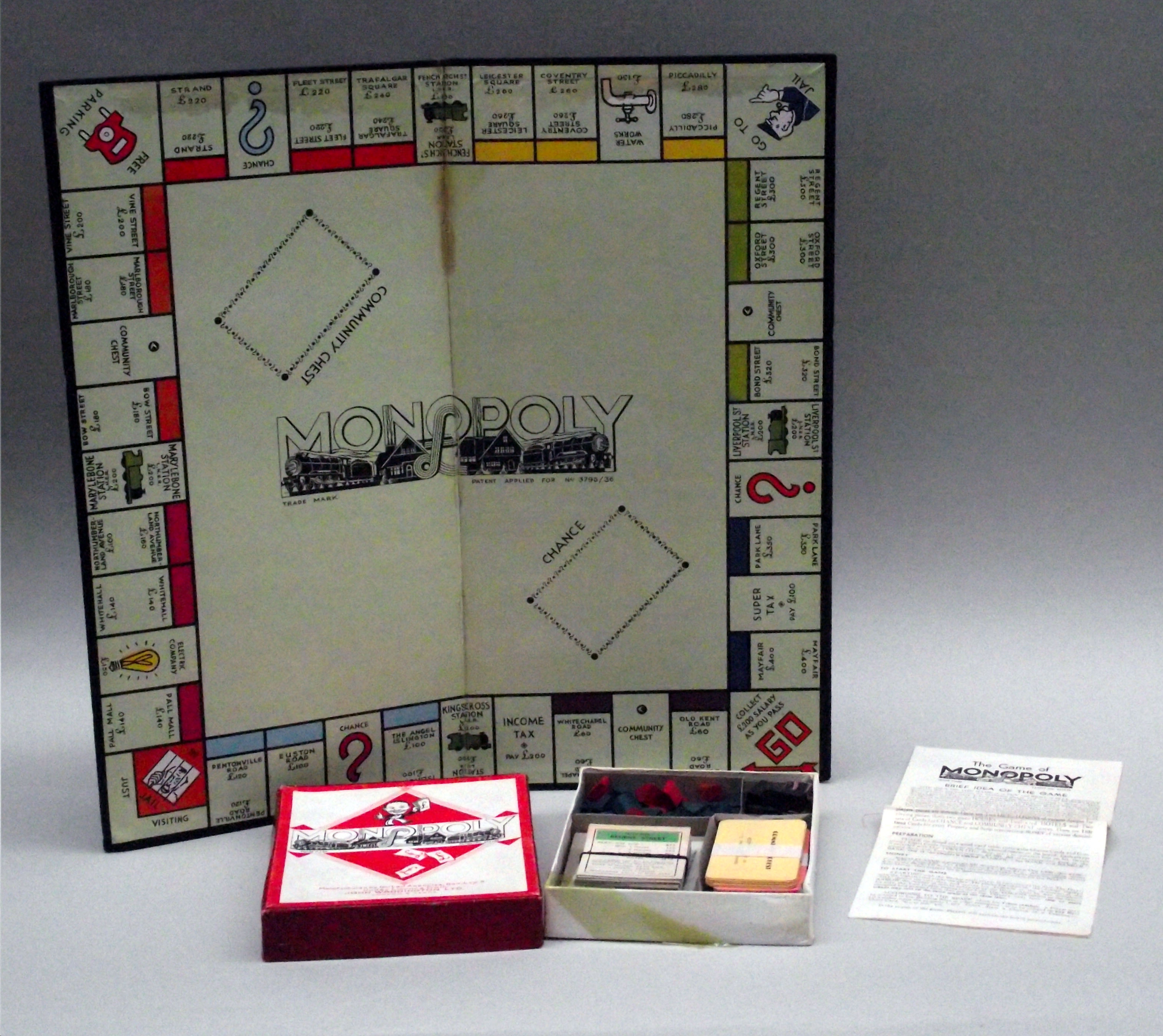 Colour photograph of a Monopoly board showing a smaller box with the cards and houses and hotels