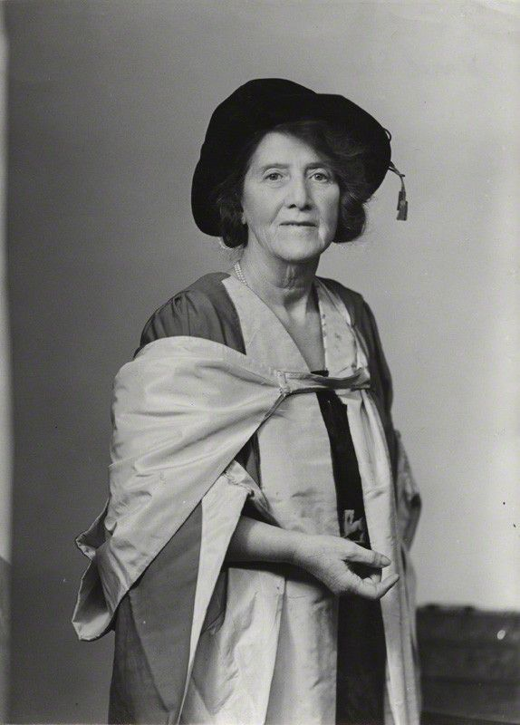 Black and white photograph.  Marie Stopes is wearing  a floppy hat (from when she received her doctorate) and an academic gown.