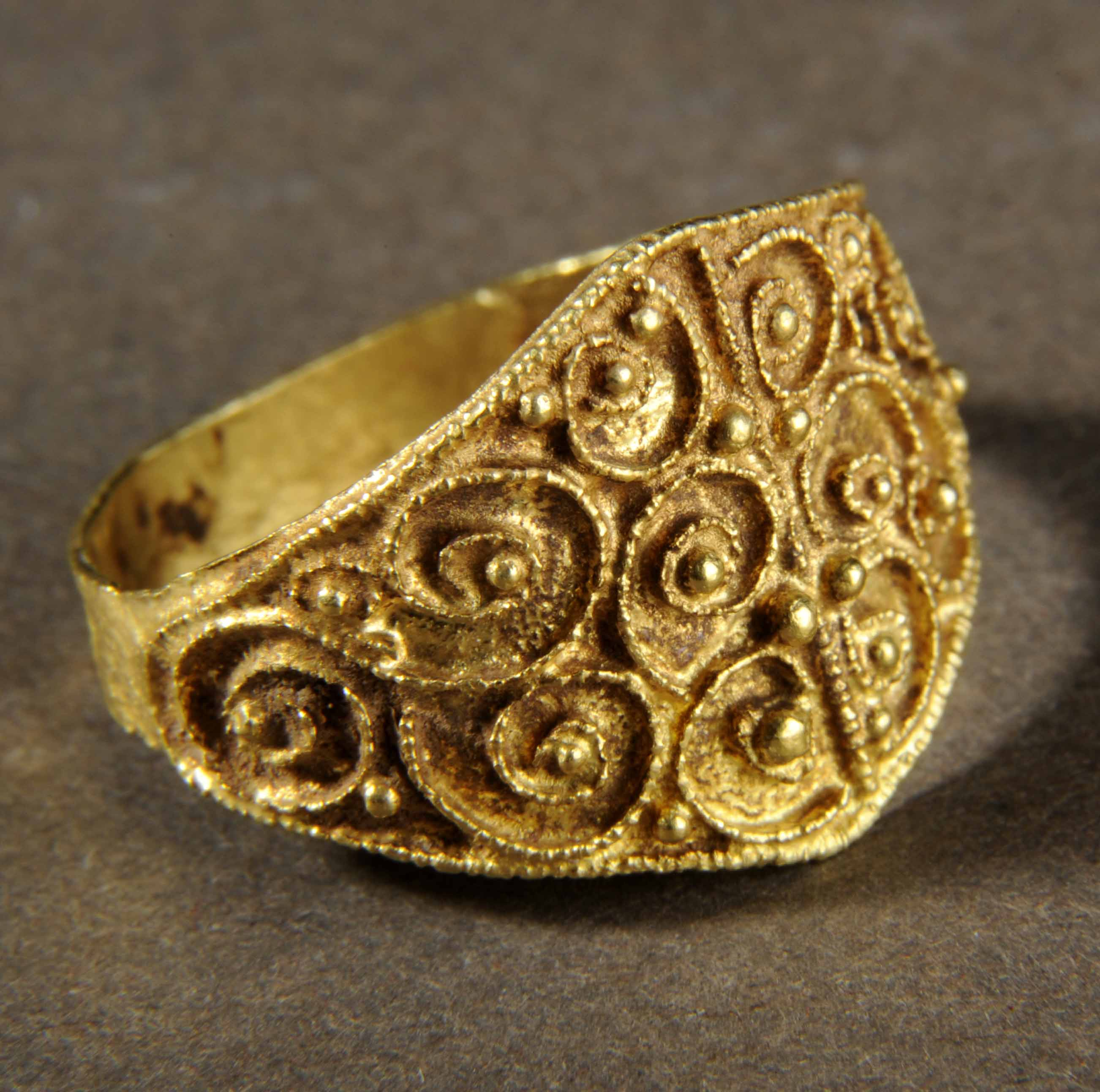 Medieval gold ring with detailed filigree design or swirls and small gold balls.