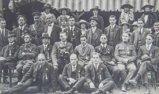 Black and white photograph showing soldiers and St. Dunstan's staff. Soldiers are wearing suits with their medals pinned to their jackets.