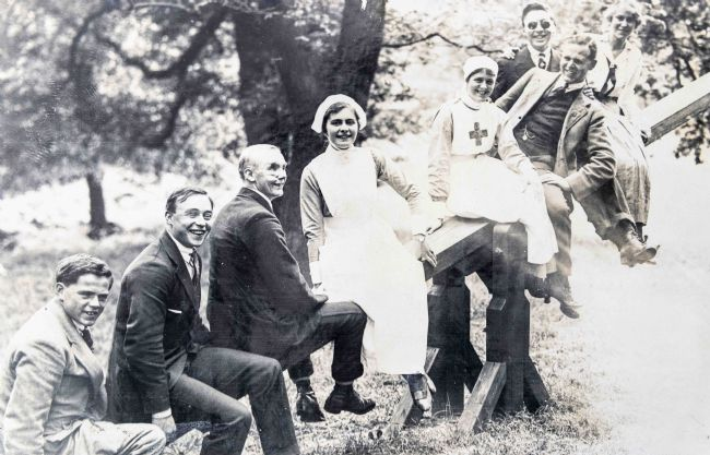 Black and white photograph of some blind veterans on a see-saw with VAD nurses.