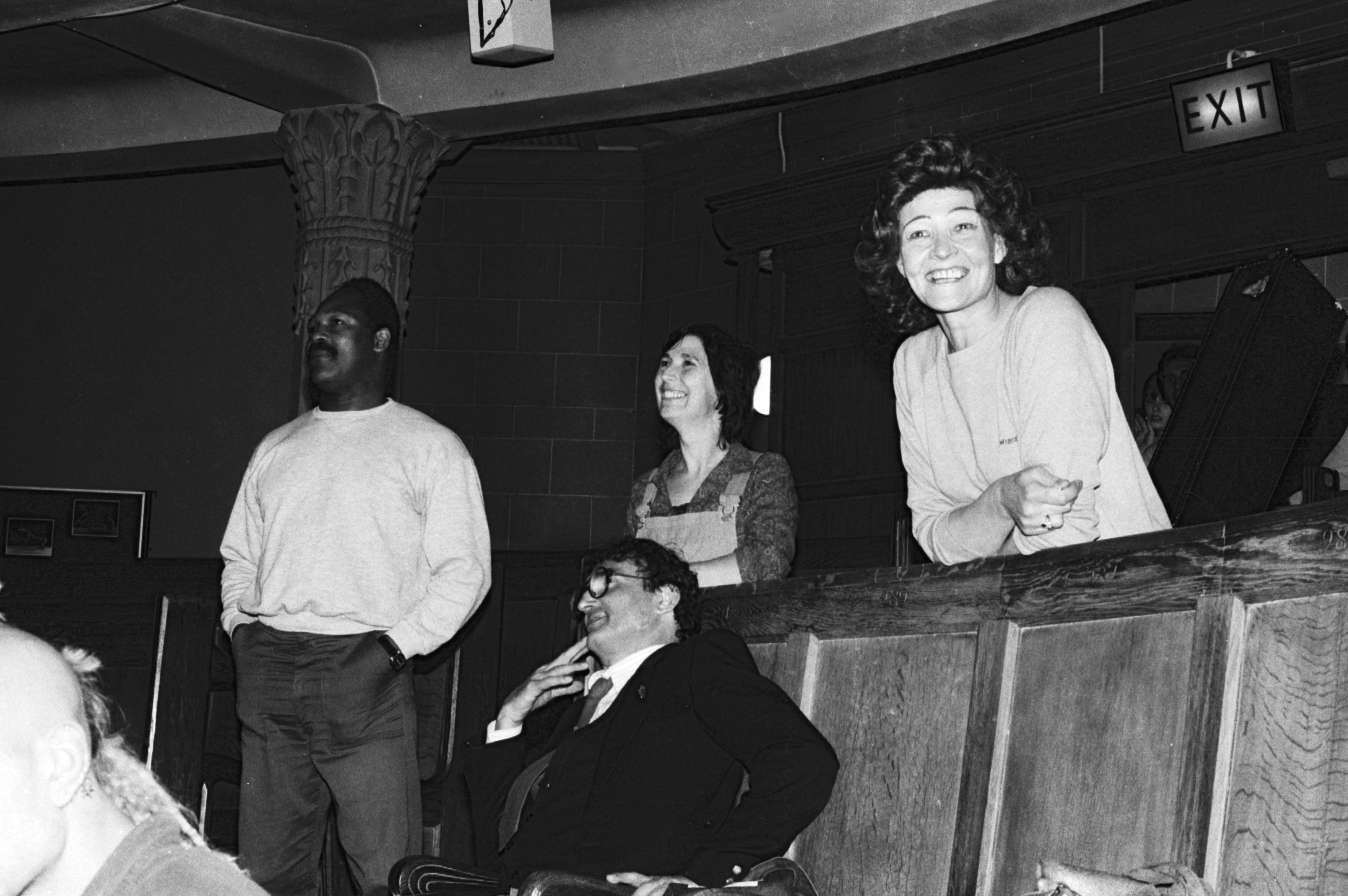 Black and white photo showing Nadine Senior leaning on theatre seats, with others