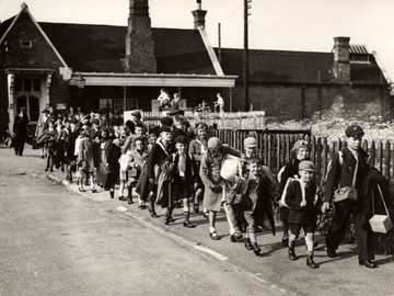 Black and white photo of a line of children walking along a pavement by the side of a fence by a railway track.