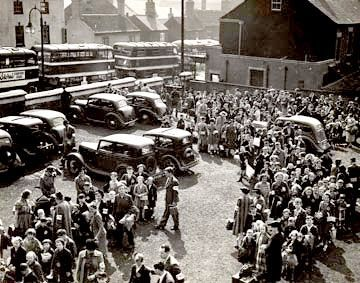 Photograph of evacuees congregating outside in Nottingham.  They are in what looks like a car park, with a line of double decker buses on the road outside.