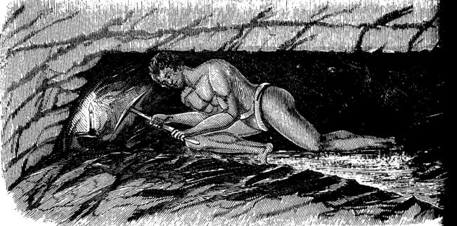 a man is hunched over in a semi lying position in a narrow tunnel.  He has a candle and a pickaxe and is working at the coalface.