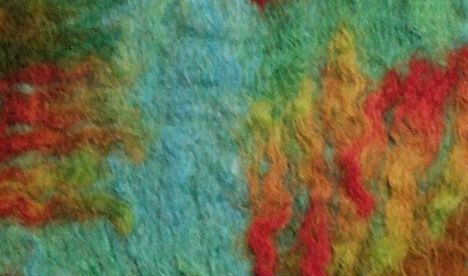 Piece of felt made from blue, gold, green and red wool.