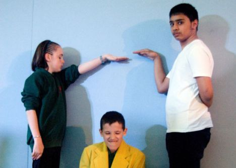 Three students acting out a painting with a live duck inside