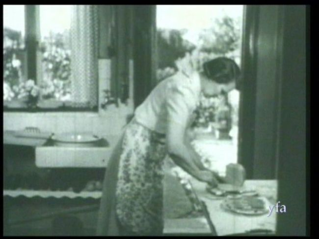 A mother preparing thinly sliced bread and butter for 1950s family tea