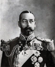Black and white portrait of King George V.  He wears a big moustache and a beard, his jacket has a high collar and tasselled epaulettes and has several medals pinned to it.