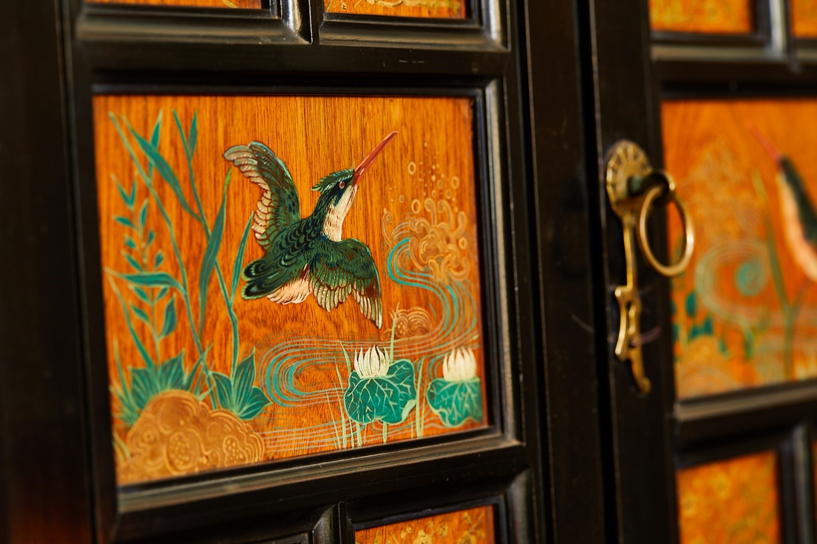 A panel of a cupboard door decorated with the image of a kingfisher by a river.
