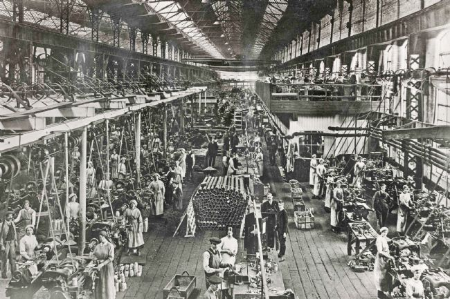 Wide view of the factory with many workers, rows of machines and piles of shell cases.