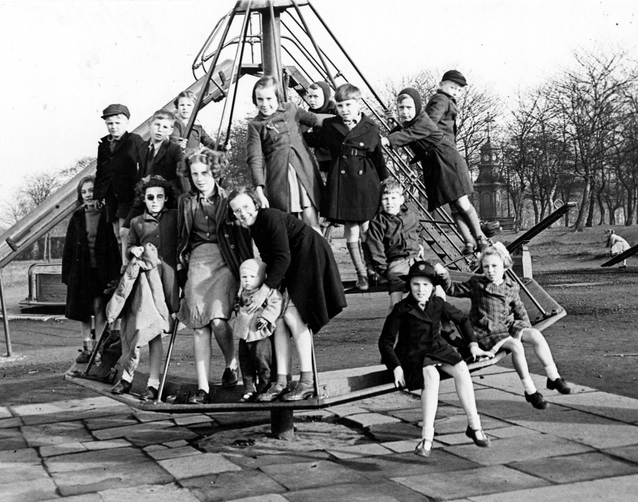 Children crowding onto a roundabout in Woodhouse Moor playground.  Paving slabs are underneath the roundabout.