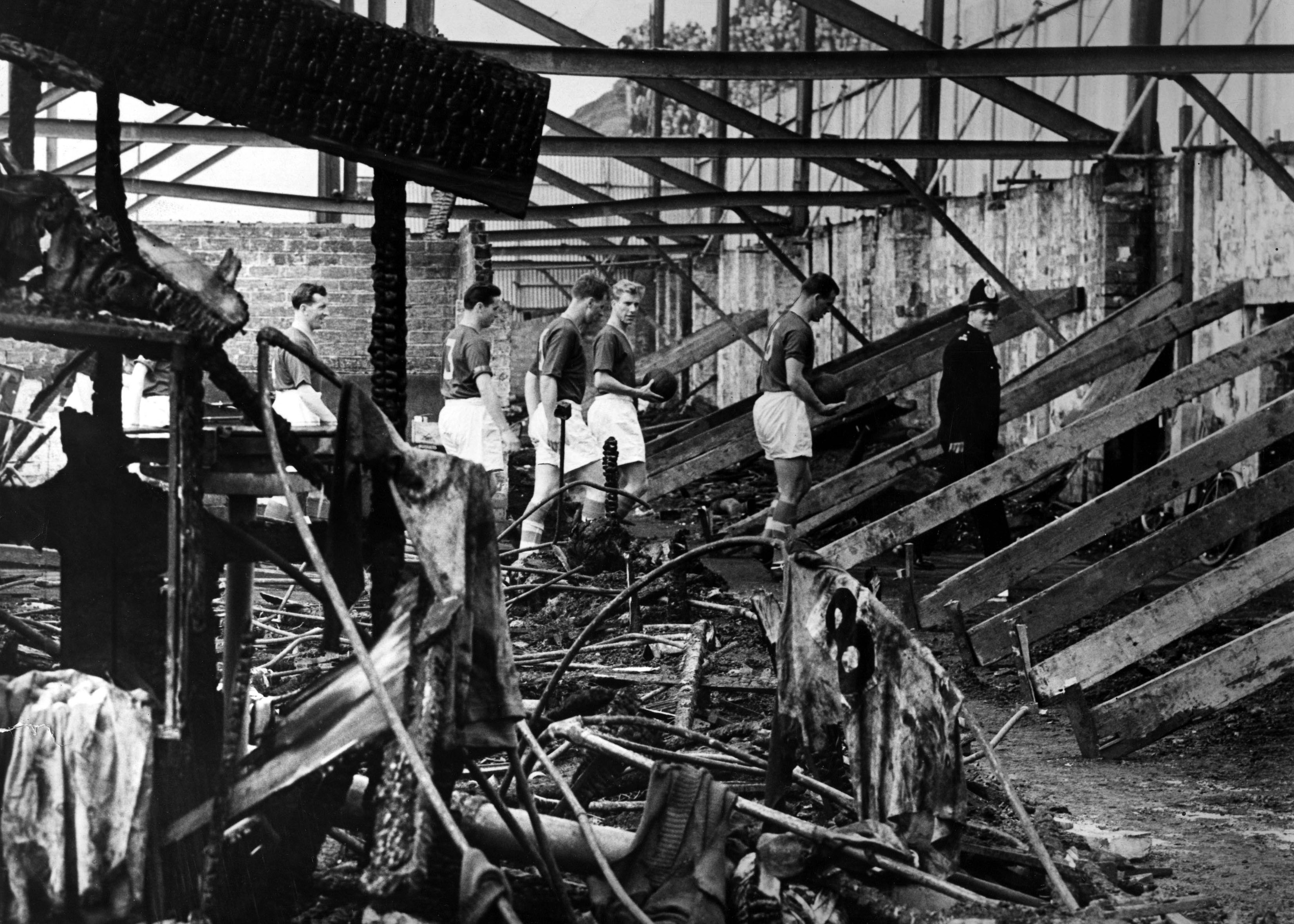 Members of the 1956 Leeds United Team inspecting the West Stand, which was completely destroyed by fire.  Image: © Leeds United Football Club