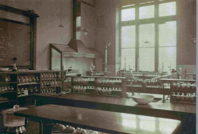 Photo of an 1890s classroom at Huddersfield Mechanical Institute showing desks and rows of glass bottles on shelves.
