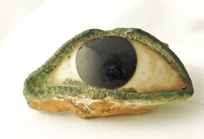 Stone or marble eye from a statue.  It looks like it has green eyeliner.