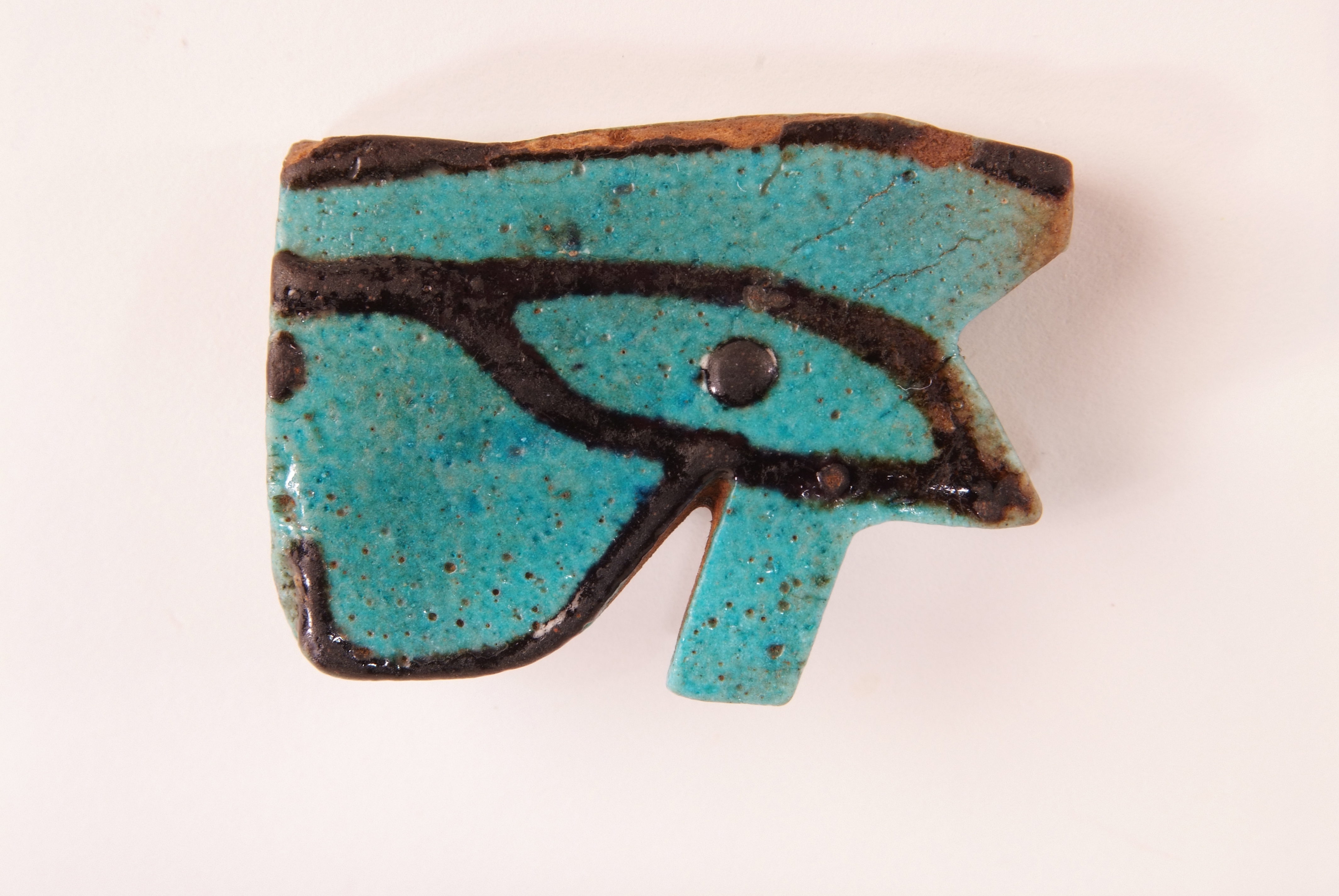 Turquoise ceramic piece made in the shape of an eye