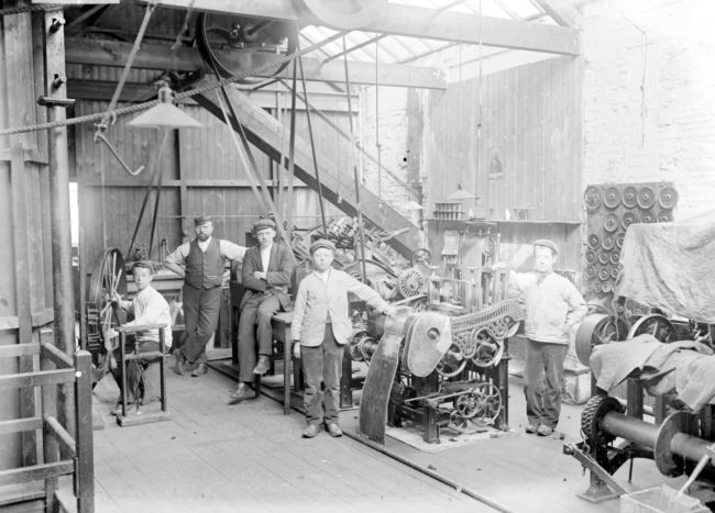 Photograph of men and children posing by their  factory machinery