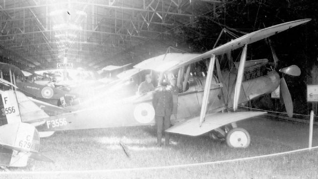 Black and white photograph of First World War aircraft with two men seated in the cockpit and one man standing by the plane