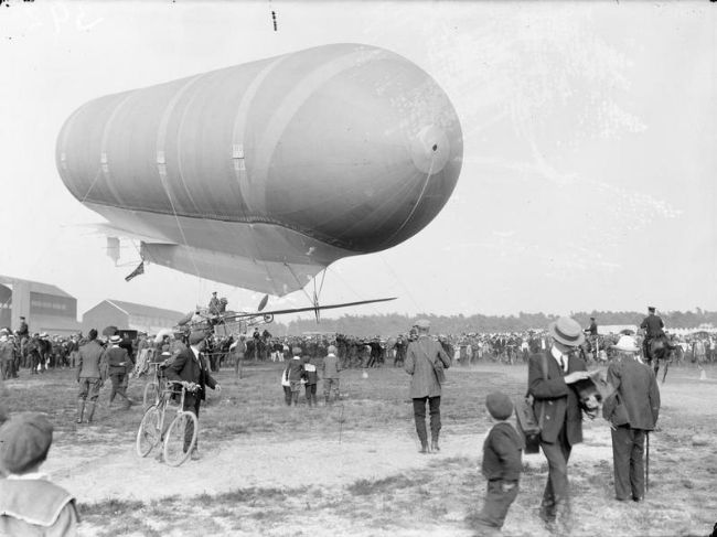Black and white photo of airship, tethered in front of a large crowd