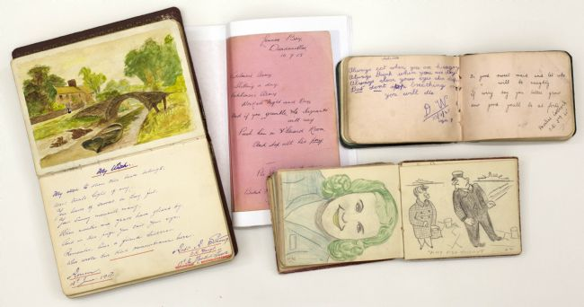 Photograph of four open WW1 autograph books showing sketches and a watercolour painting