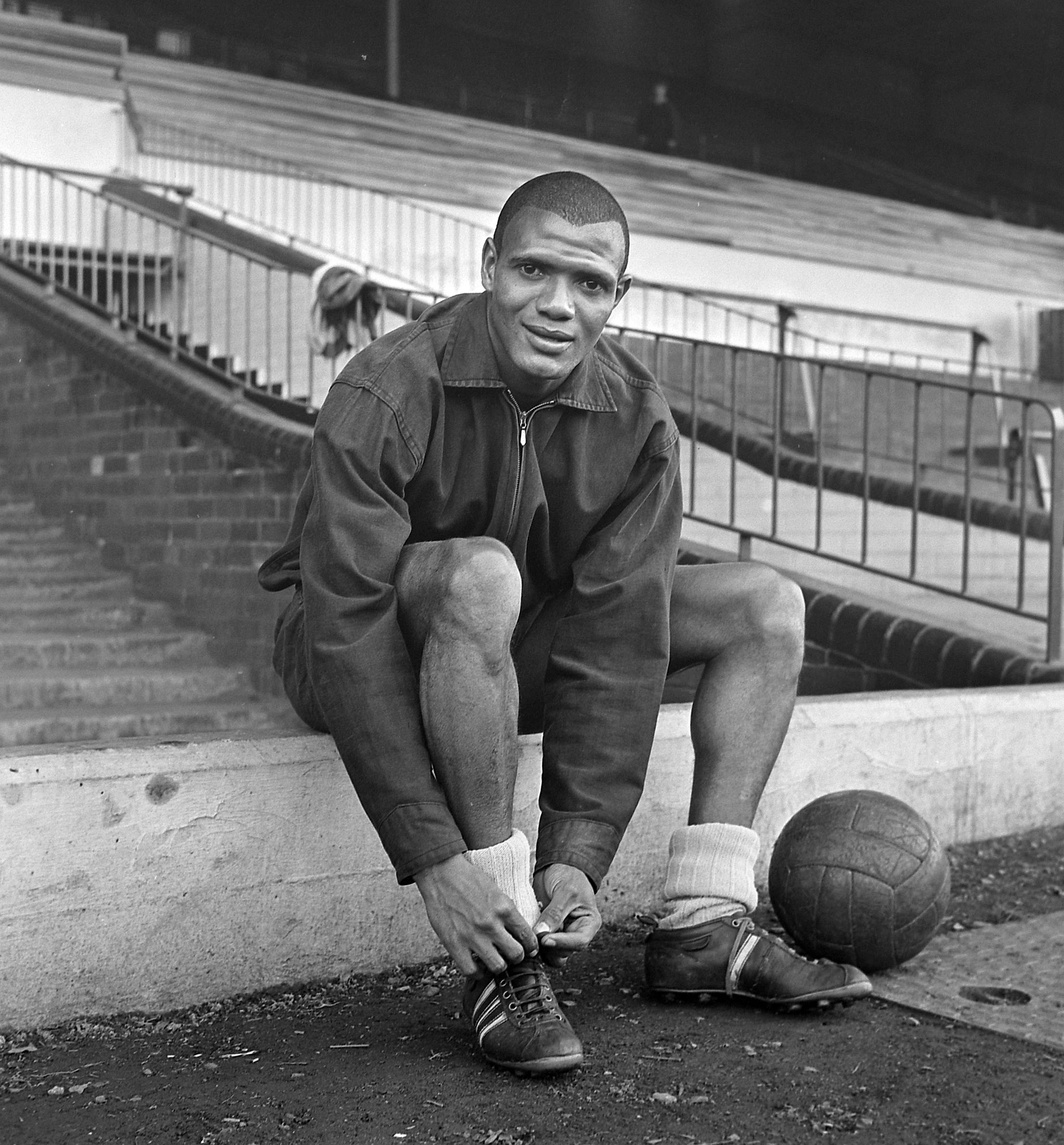 Black and white photograph of Albert sitting on some steps tying up his football boots